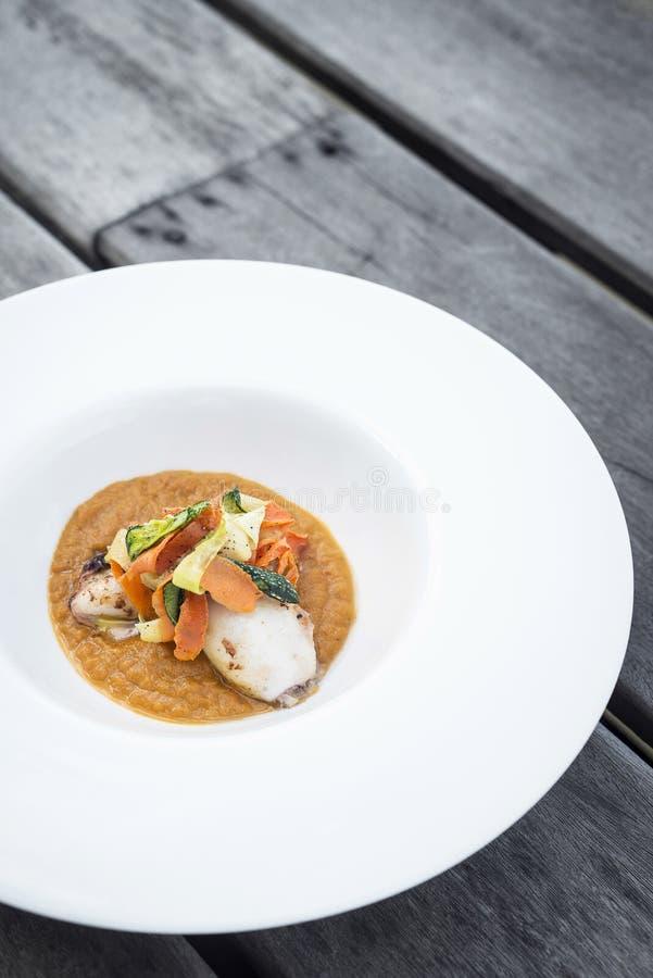 Feinschmecker füllte Kalmar mit Gemüse im Kürbiscurrypüree an lizenzfreie stockbilder