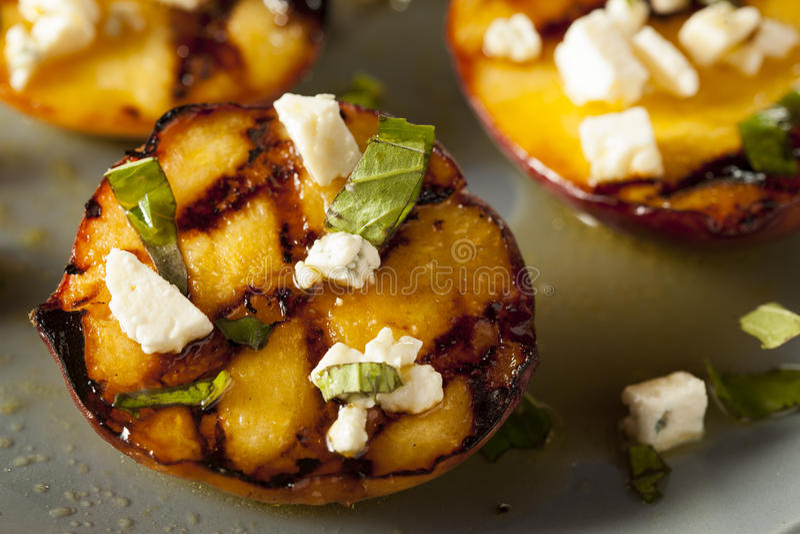 Feinschmecker gebratene Pfirsiche mit Käse und Basilikum lizenzfreies stockfoto