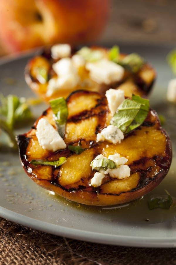 Feinschmecker gebratene Pfirsiche mit Käse und Basilikum lizenzfreie stockfotografie