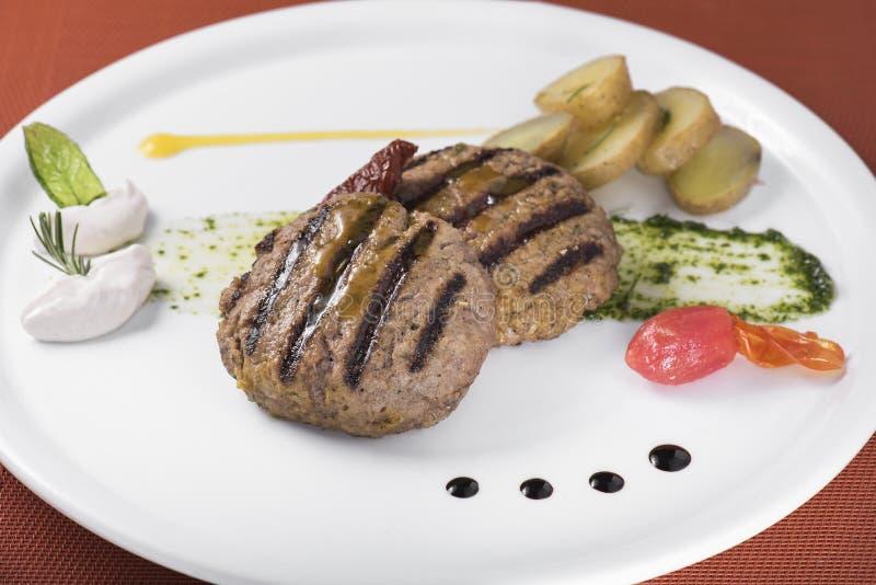 Feinschmecker gegrillter Beefburger mit poschierten Kartoffeln 2 lizenzfreie stockfotografie