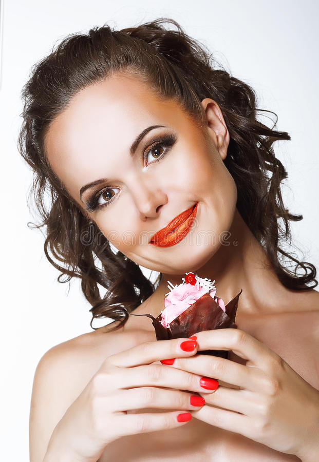 Feinschmecker. Glückliche junge Frau, die kleinen Kuchen mit Schlagsahne hält stockfotos