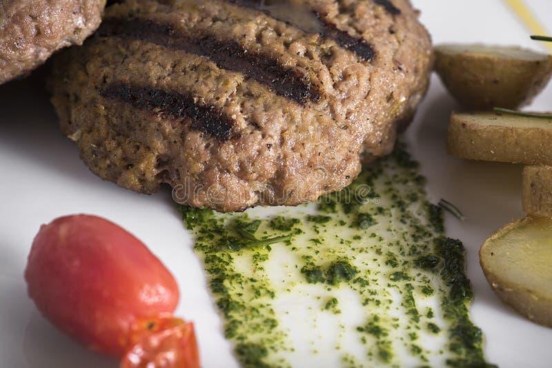 Feinschmecker grillte Beefburger mit poschierten Kartoffeln 11close herauf Schuss lizenzfreie stockbilder