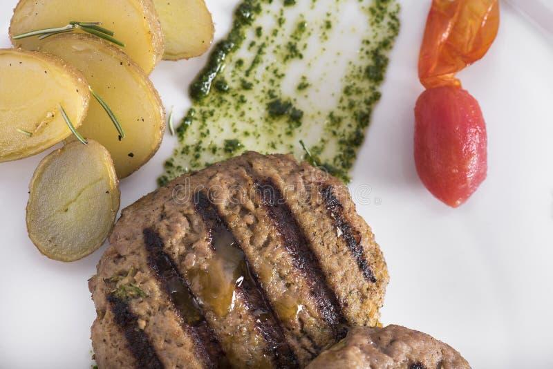 Feinschmecker grillte Beefburger mit poschierten Kartoffeln 12close herauf Schuss lizenzfreies stockfoto