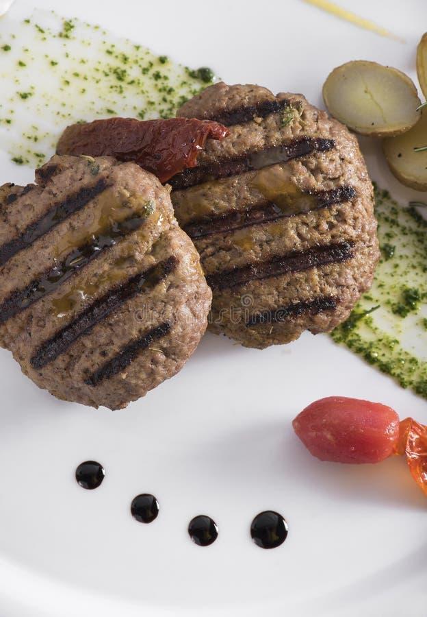 Feinschmecker grillte Beefburger mit poschierten Kartoffeln 14close herauf Schuss lizenzfreie stockbilder