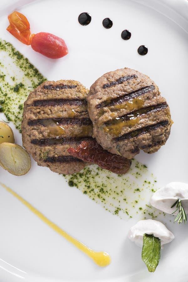 Feinschmecker grillte Beefburger mit poschierter Ansicht der Kartoffeln 6top stockfotografie