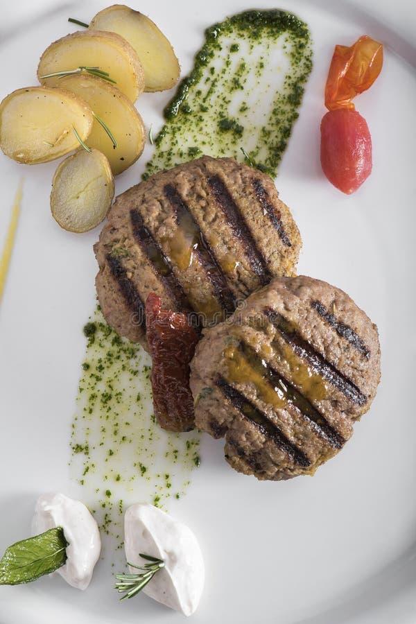 Feinschmecker grillte Beefburger mit poschierter Ansicht der Kartoffeln 7top stockfoto