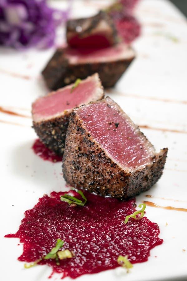 Feinschmecker verbrannte Thunfisch in der Kruste des schwarzen Pfeffers mit Rote-Bete-Wurzeln coulis lizenzfreies stockfoto