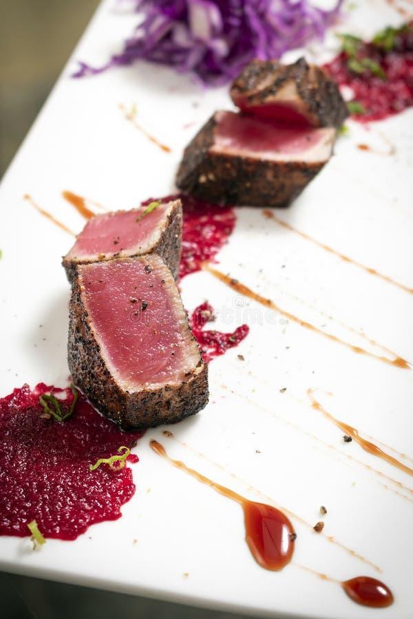 Feinschmecker verbrannte Thunfisch in der Kruste des schwarzen Pfeffers mit Rote-Bete-Wurzeln coulis lizenzfreie stockbilder