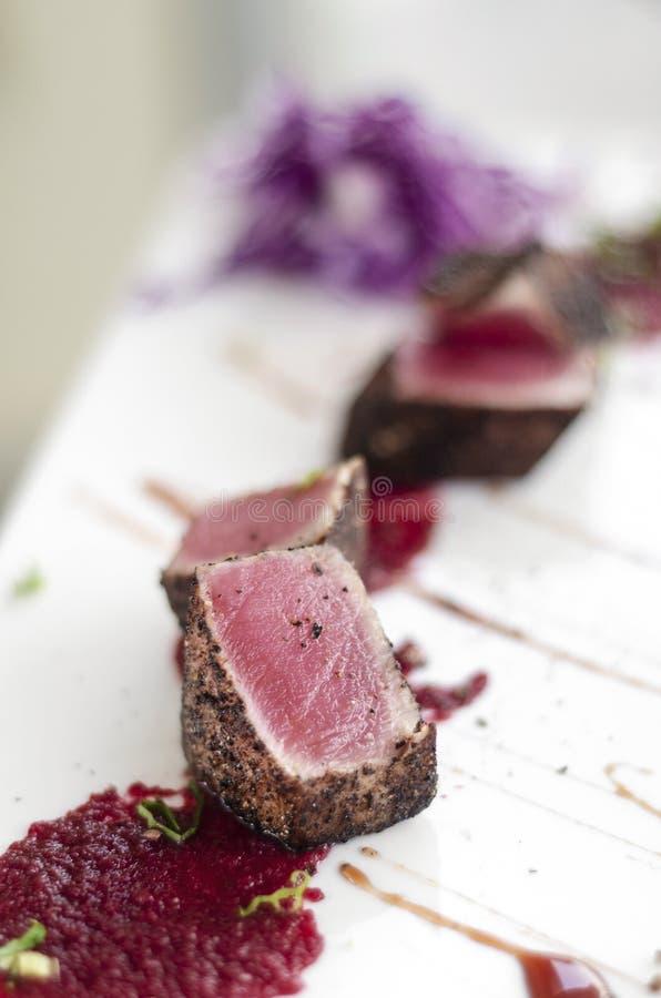 Feinschmecker verbrannte Thunfisch in der Kruste des schwarzen Pfeffers mit Rote-Bete-Wurzeln coulis stockbild