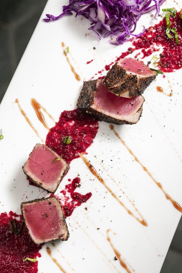 Feinschmecker verbrannte Thunfisch in der Kruste des schwarzen Pfeffers mit Rote-Bete-Wurzeln coulis stockfotos