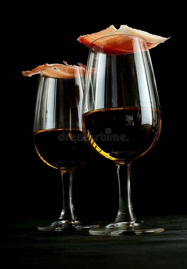Feinschmeckerischer Schinken balancierte auf Gläsern spanischem Sherry lizenzfreies stockfoto