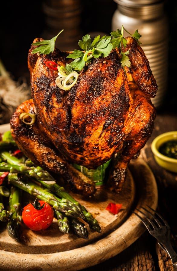 Feinschmeckerisches geschmackvolles gegrilltes Bier-Dosen-Hühnerfleisch auf hölzernem Brett stockfotografie