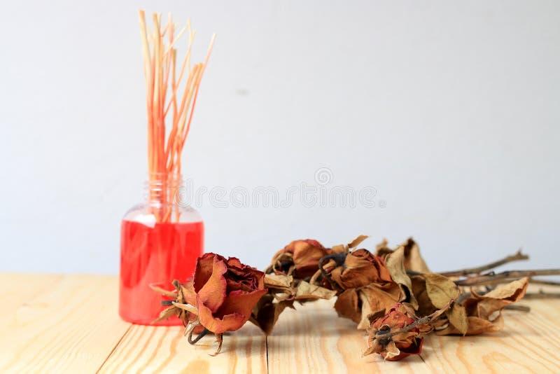 Feito à mão do difusor da fragrância ajustado: a garrafa com varas do aroma e a rosa seca do vermelho cobrem os difusores, uma ga fotografia de stock royalty free
