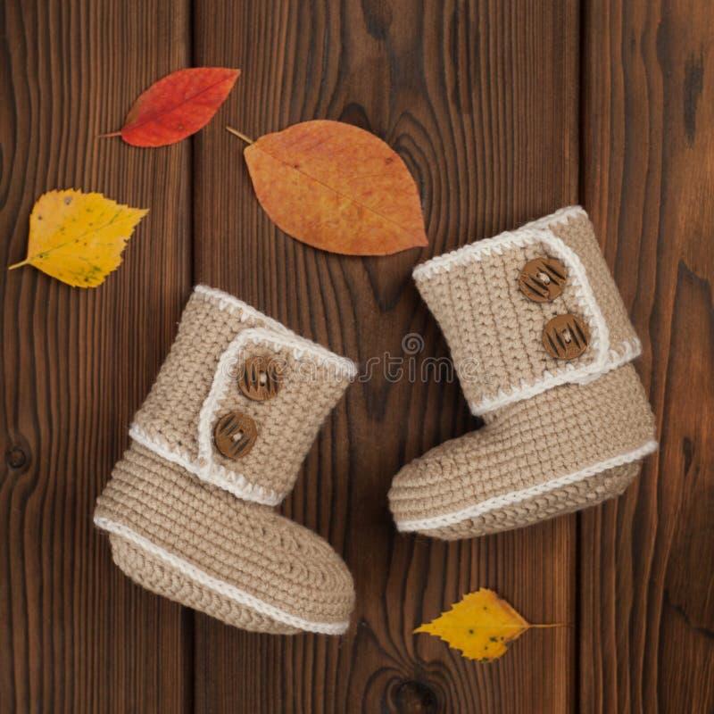 Feito à mão fazer crochê montantes do bebê e as folhas multi-coloridas caídas outono no fundo de madeira imagens de stock royalty free
