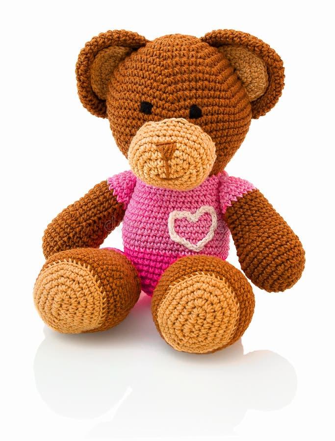 Feito a mão bonito faz crochê a boneca do urso no fundo branco com reflexão da sombra imagem de stock