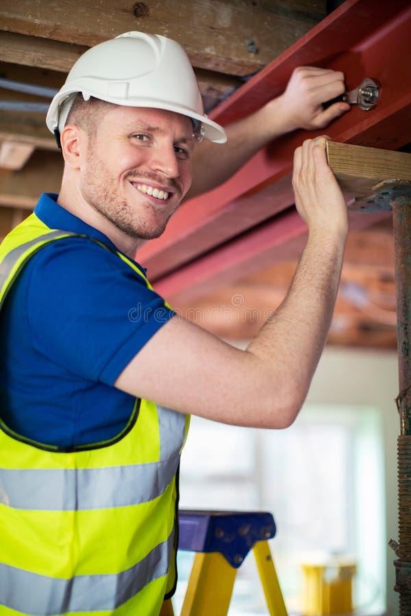 Feixe de apoio de aço cabendo do trabalhador da construção no teto renovado da casa fotos de stock
