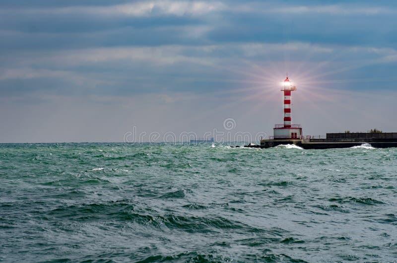 Feixe do holofote do farol através do ar marinho Farol na paisagem tormentoso - líder And Vision Concept foto de stock royalty free