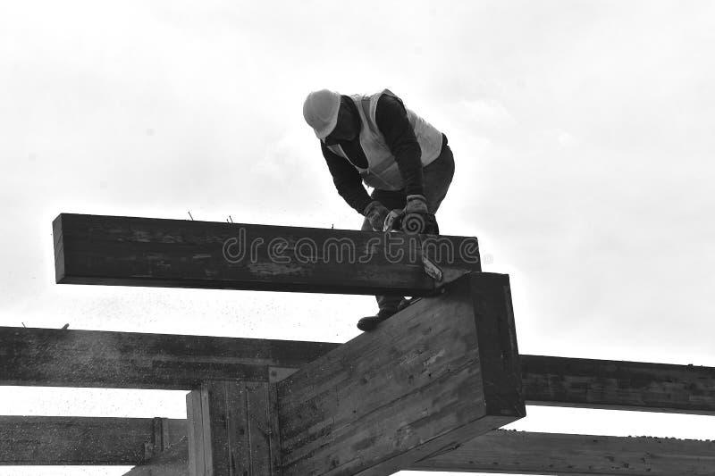 Feixes das serras do trabalhador da construção em um projeto da demolição foto de stock