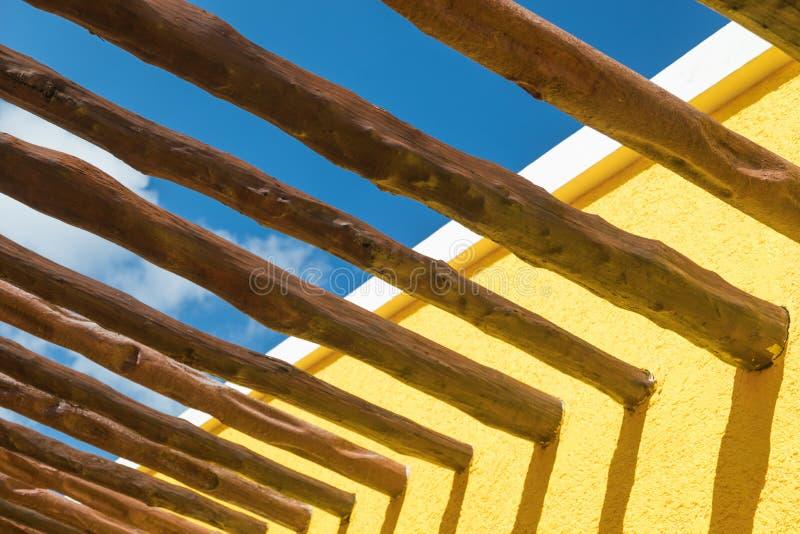 Feixes de madeira abstratos do cargo e parede amarela brilhante contra o céu azul fotos de stock