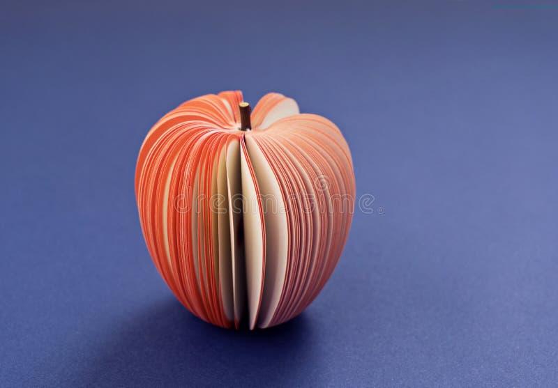 Fejka Apple från papper på den purpurfärgade bakgrunden royaltyfri bild