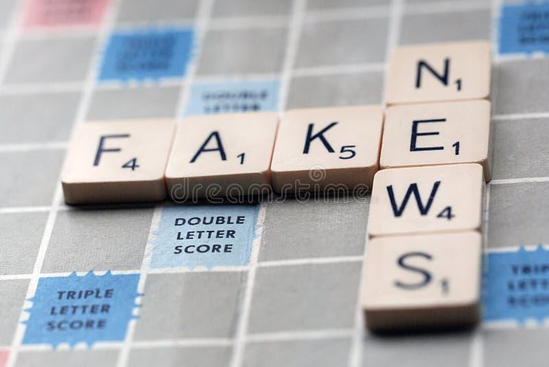 Fejka nyheterna - begreppet av fejkar nyheterna på ett Scrabblebräde royaltyfri foto