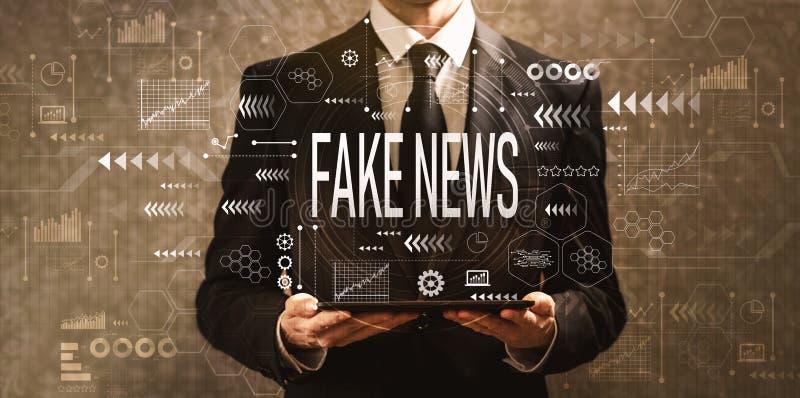Fejka nyheterna med affärsmannen som rymmer en minnestavladator royaltyfri bild