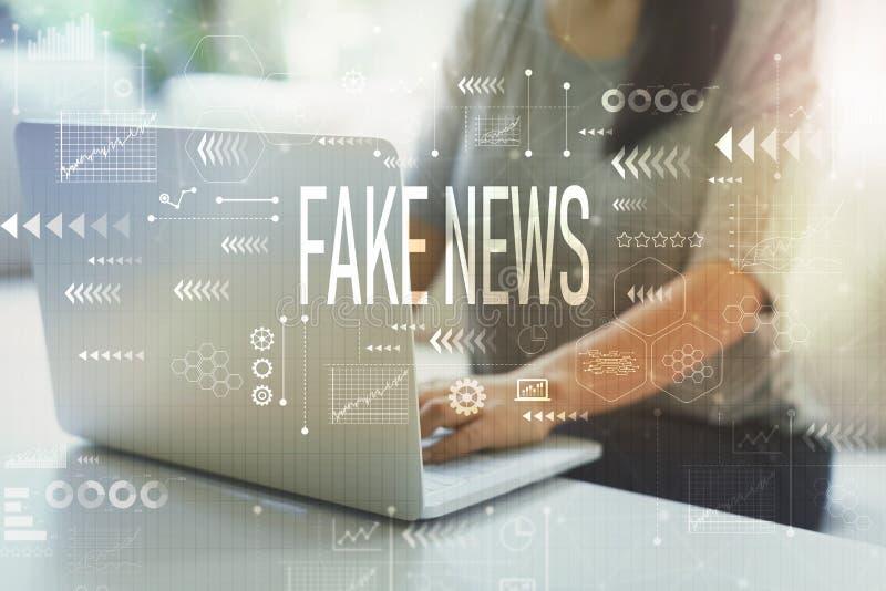 Fejka nyheterna med kvinnan som använder bärbara datorn royaltyfri foto