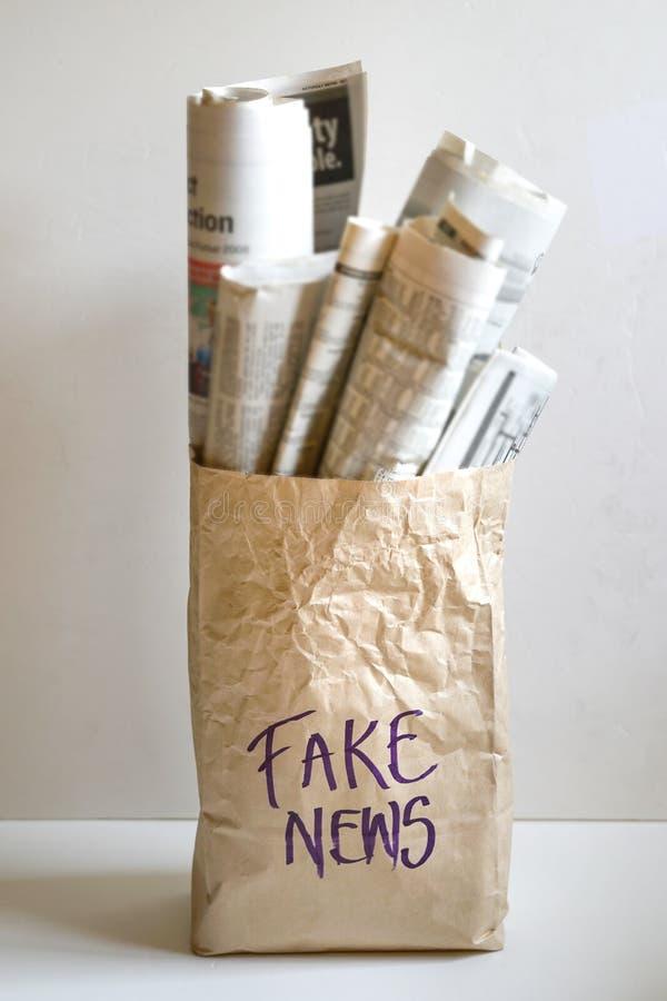 Fejka nyheternabegreppet: en pappers- påse som fylls med tidningar, och ordet fejkar nyheterna på den royaltyfria bilder