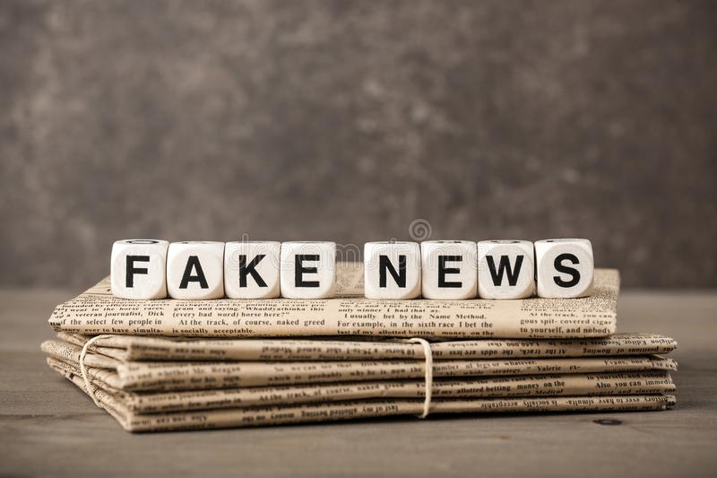 Fejka nyheternabegreppet med tidningar och kuber med bokstäver royaltyfri fotografi