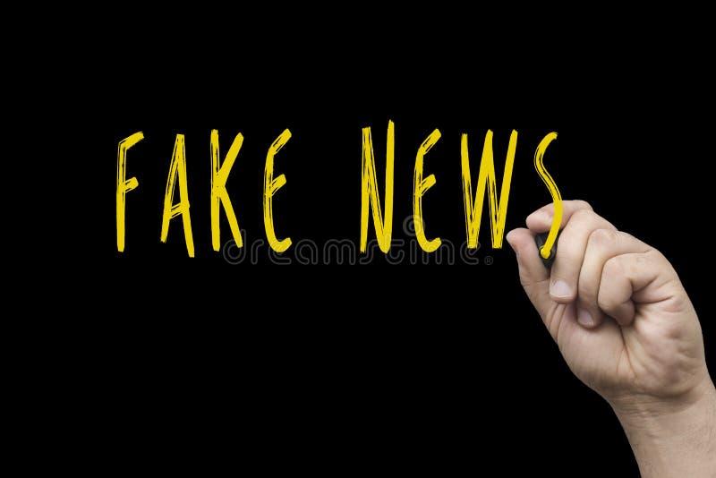 Fejka nyheternaord som är skriftliga i krita på svart bräde royaltyfria foton