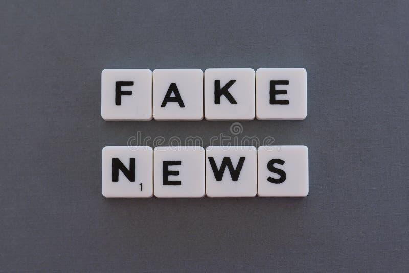 Fejka nyheternaordet gjorde av fyrkantigt bokstavsord p? gr? bakgrund arkivbilder