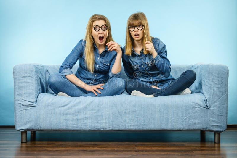 Fejkar rymma för två chockat kvinnor glasögon på pinnen fotografering för bildbyråer