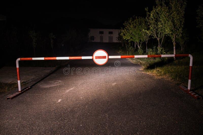 Fel vägbegrepp Barriär med tecknet inget tillträde på natten Barriäranseende på vägen till den läskiga spökade byggnaden med spök royaltyfria foton