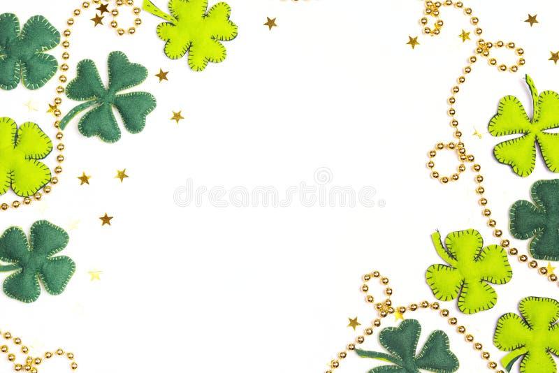 Feld des Filzvierblättrigen kleeblattes und -Goldperlen auf weißem backgro stockbilder