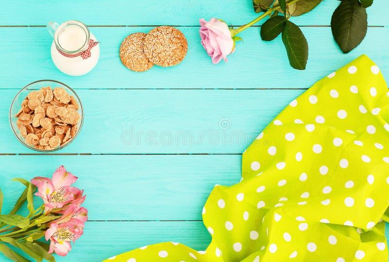 Feld des Morgenlebensmittels mit Krug Milch, Plätzchen und Haferflocken auf blauem hölzernem Hintergrund Tischdecke und Blumen Be lizenzfreie stockfotografie