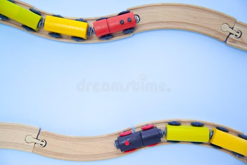 Feld für den Text gemacht von den Mehrfarbenkinderschienenfahrzeugziegelsteinen auf hölzerner Eisenbahn auf blauem Hintergrund Co lizenzfreies stockbild