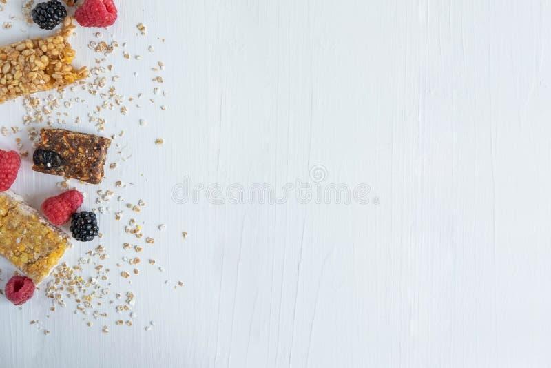 Feld für Text mit Granola und natürlichen Beeren von Blaubeeren, von Himbeere, von Blaubeere und von Hafermehl auf einem weißen h lizenzfreie stockfotografie