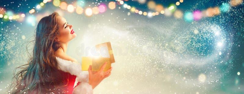 Feld Feiertagshintergrund Junge Frau Schönheit Brunette in der Parteikostüm-Öffnungsgeschenkbox lizenzfreies stockfoto