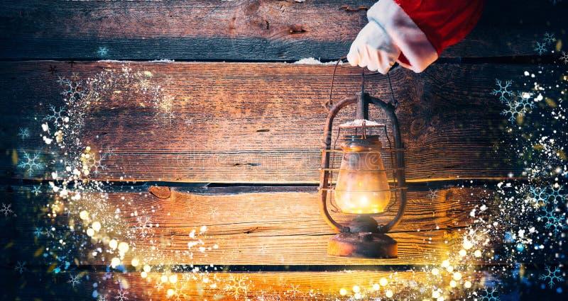 Feld Feiertagshintergrund Santa Claus-Hand, die Weinleseöllampe hält lizenzfreie stockfotos