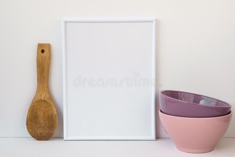 Feld Modell auf weißem Hintergrund, bunte keramische Schüsseln, hölzerner Löffel, angeredetes Bild für Social Media lizenzfreies stockfoto