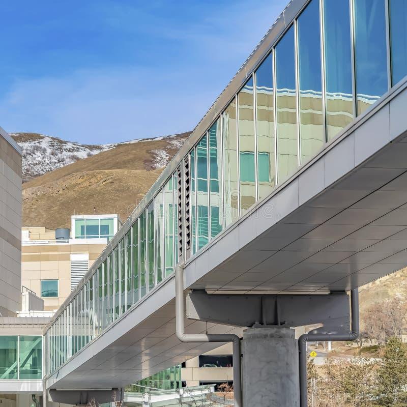 Feld Skybridge angeschlossen an ein modernes Gebäude mit Gebirgs- und des blauen Himmelshintergrund stockbilder