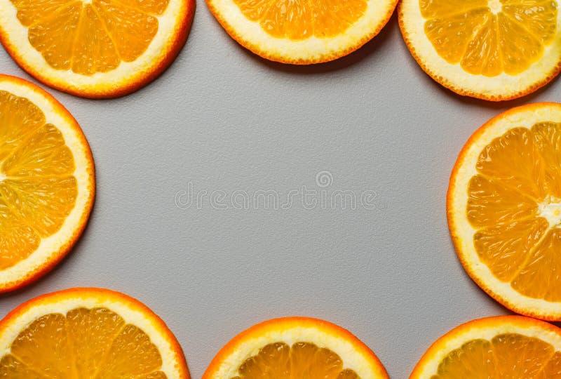 Feld von den Rundschnitt Scheiben von reifen saftigen organischen Orangen auf grauem Hintergrund Draufsichtebenenlage Vibrant Far lizenzfreies stockbild