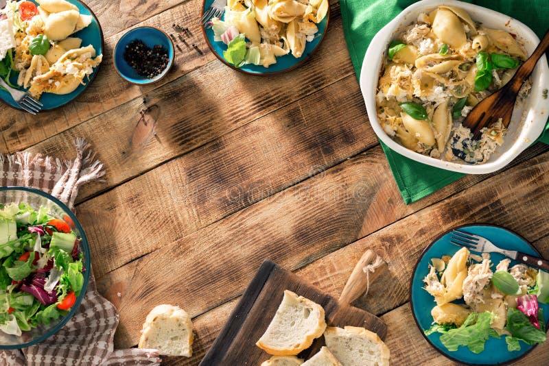 Feld von italienischen Teigwaren mit Salat auf Holztisch lizenzfreies stockbild