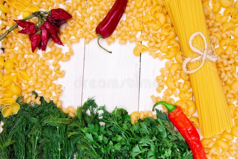 Feld von Vielzahl von italienischen Teigwaren und von Gemüse auf hölzernem Schreibtisch stockbilder