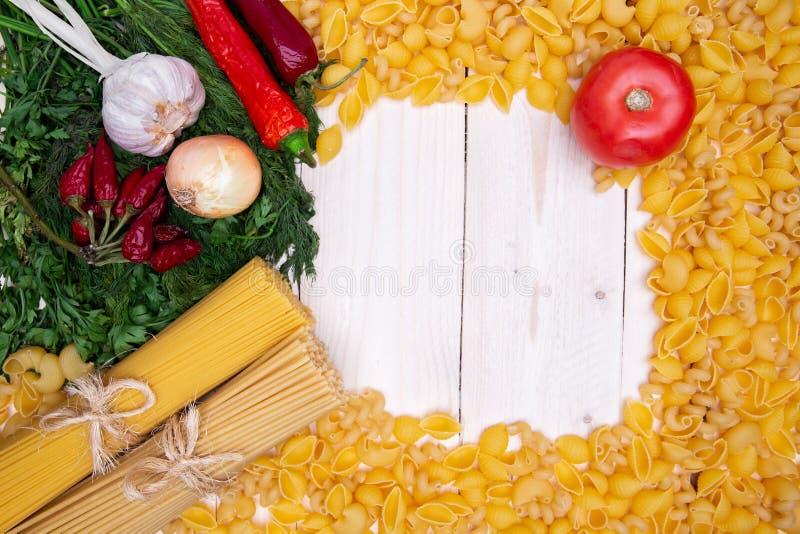 Feld von Vielzahl von italienischen Teigwaren und von Gemüse auf hölzernem Schreibtisch stockfotos