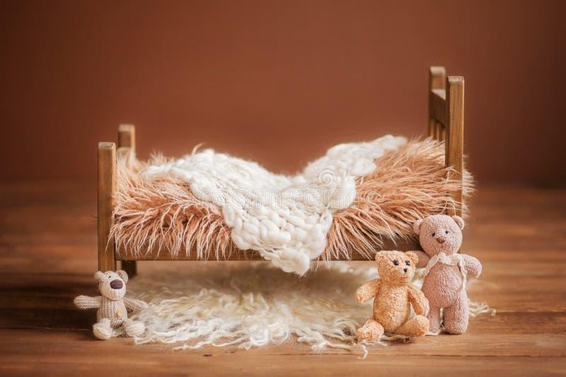 Feldbett für ein neugeborenes auf einem braunen Hintergrund mit Spielwaren und einer weißen Wolldecke, Hintergrund stockfotografie
