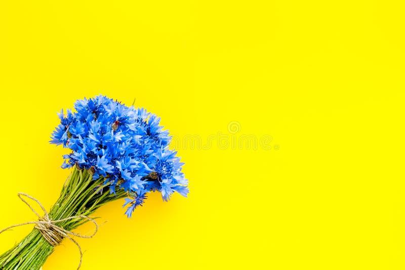 Feldblumen entwerfen mit Blumenstrauß von blauen Kornblumen auf gelbem Draufsichtraum des Hintergrundes für Text stockfotografie