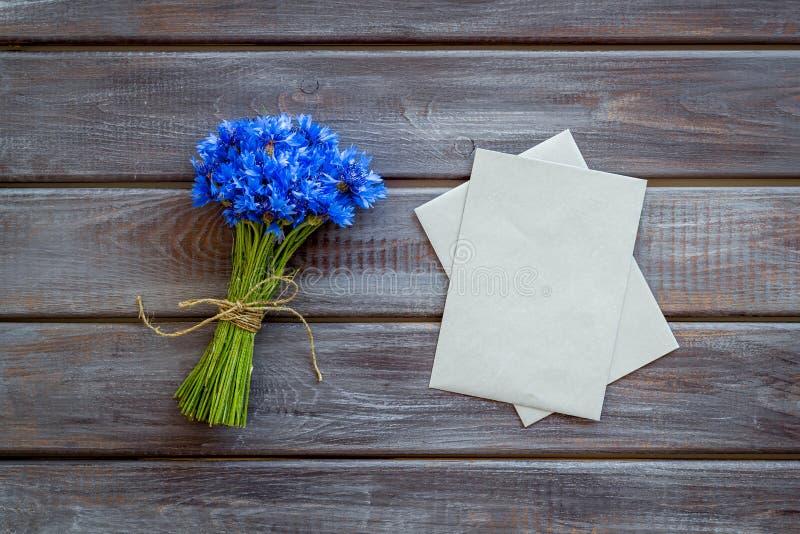 Feldblumen entwerfen mit Blumenstrauß von blauen Kornblumen und von Umschlägen für Geschenk auf hölzernem Draufsichtmodell des Hi lizenzfreie stockfotos