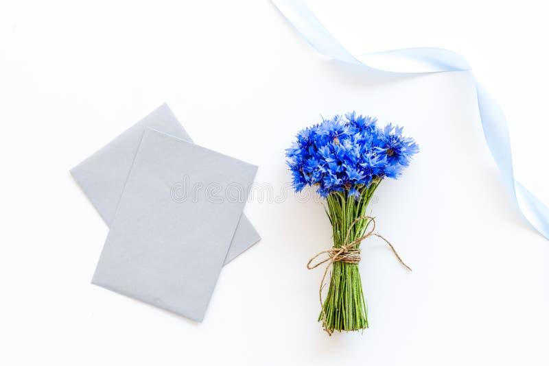 Feldblumen entwerfen mit Blumenstrauß von blauen Kornblumen und von Umschlägen für Geschenk auf weißem Draufsichtmodell des Hinte lizenzfreies stockfoto