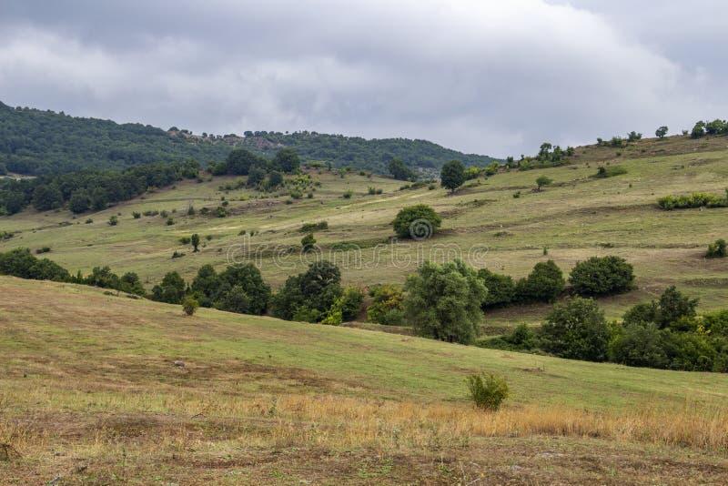 Felder und Hügel am Fuß des Rhodopes unter drastischem stürmischem Himmel stockbild